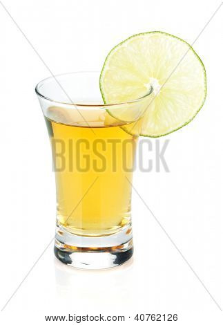 Shot of gold tequila with lime slice. Isolated on white background