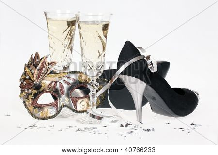 Masquerade mask, champagne and high heel shoes isolated on white background.