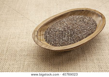 chia seeds in a rustic oval wood bowl against canvas