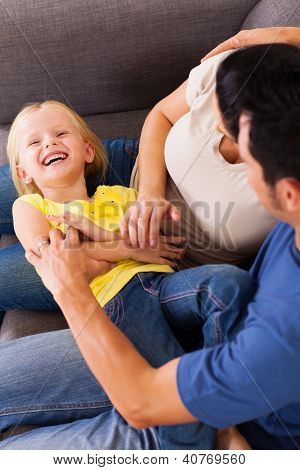 parents tickling little daughter on sofa