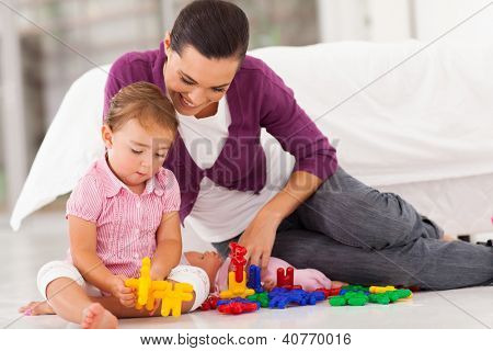 loving mother watching daughter playing with toy