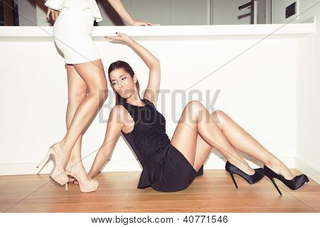 couple of young women in elegant dresses and high heel shoes indoor shot