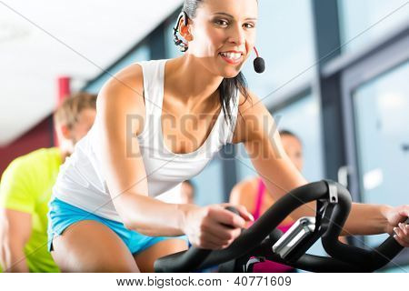 Young People - group of women and men - doing sport in the gym for fitness