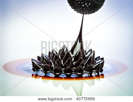 Macro photograph of Ferrofluid flowing from one magnet to another. Ferrofluid is a colloidal liquid of nanoscale particles in a carrier fluid that becomes magnetized by approaching a magnet.