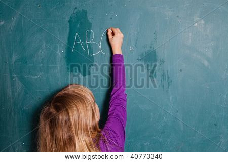 Young Girl Writing Letters On Chalkboard