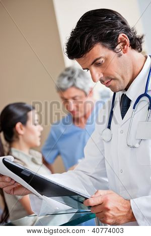 Mixed race male doctor reading document while colleagues standing at reception