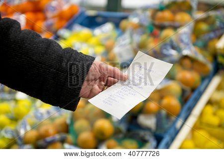 Mano, una lista de compras con compras del día a día delante de cajones con frui fresco, colorido