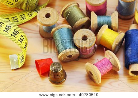 Reels Of Thread  Tapeline And Two Thimbles On Wooden Table
