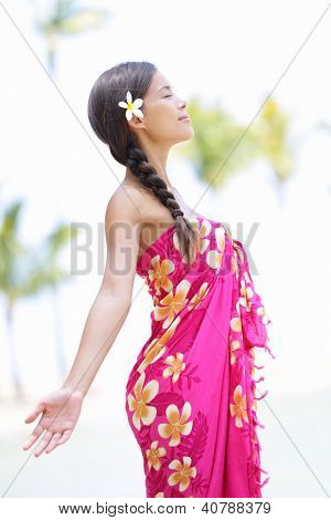 Beach woman on Hawaii relaxing enjoying the sun in serene relaxed pose. Hawaiian scene with beautiful mixed race Asian and Caucasian female model wearing sarong.