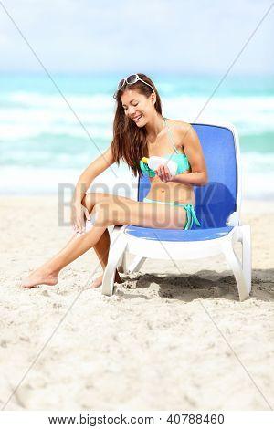 Mujer en la playa de aplicar bloqueador / protector solar en las piernas sonriendo feliz sentado en bikini en sunb