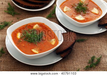 Image of bowls of hot red soup served with bread on a beige tablecloth