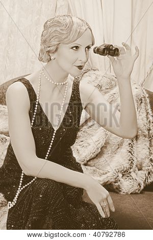 Old photo with reenacted scene of a classy lady in roaring twenties style using a pair of opera glasses - grain has been added for vintage photo look