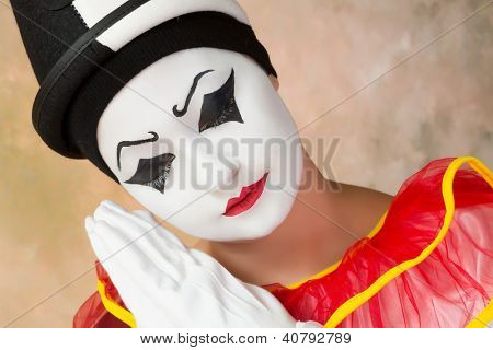 Sad or serious clown acting in pierrot disguise