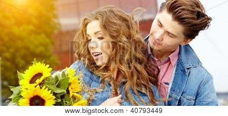 Loving young man hugging his girlfriend with sunflowers in their hands