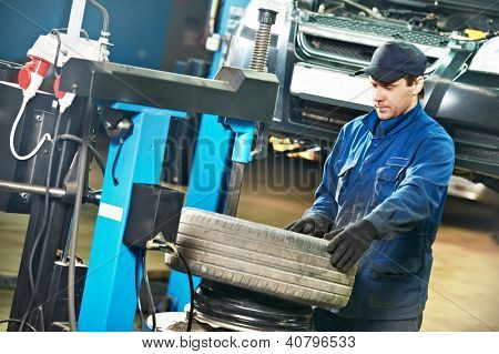 auto mechanic repairman at car tyre replacement and balancing adjustment using special equipment