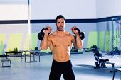 pic of kettlebell  - man lifting kettlebell workout exercise at gym - JPG