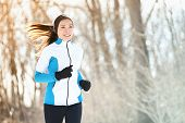 Running sport woman. Female runner jogging in cold winter forest wearing warm sporty running clothin