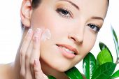 stock photo of beautiful face  - Woman applying moisturizer cream on face - JPG