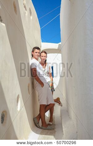 Young Couple Walking In Old Greek Village On Santorini Island, Greece