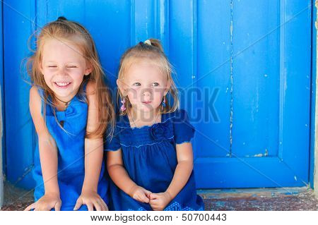 Closeup Of Little Adorable Girls Sitting Near Old Blue Door In Greek Village, Emporio, Santorini