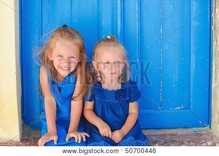 Portrait Of Little Adorable Girls Sitting Near Old Blue Door In Greek Village, Emporio, Santorini