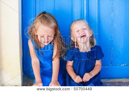 Portrait Of Little Smiling Girls Sitting Near Old Blue Door In Greek Village, Emporio, Santorini