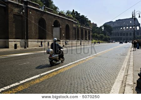 Scooter Drives Towards The Colloseum In Rome