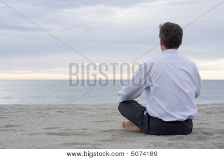 Businessman Meditating At The Sea