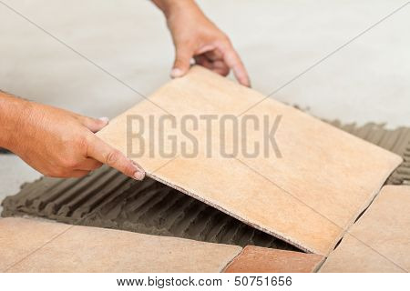 Man Lays Ceramic Floor Tiles - Closeup