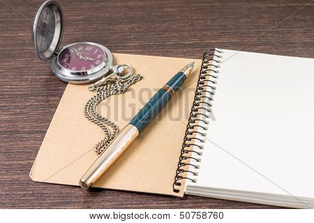 Opened Notebook With Ink Pen And Pocket Watch On Wooden Table