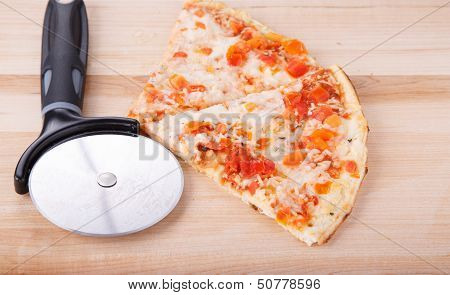 Pizza And Cutting Wheel On Wood Board