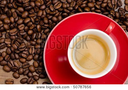 Red Cup Of Espresso With Brown Coffee Beans