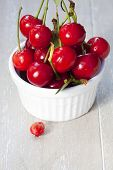stock photo of picking tray  - Freshly picked cherries with stem and leaves in a white bowl in front is a cherry pit - JPG