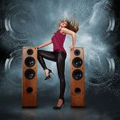 foto of subwoofer  - Abstract concept of powerful audio speakers blast out a cloud of dust against dark background and dancing woman posing in front of them - JPG