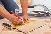 stock photo of ceramic tile  - Laying ceramic floor tiles - man hands marking tile to be cut closeup