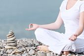 image of mudra  - hand of a woman meditating in a yoga pose on the beach - JPG
