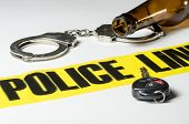 stock photo of handcuffs  - Police tape with a beer bottle handcuffs and car key - JPG