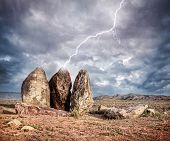 stock photo of nomads  - Lightning strikes three big stones in the steppe of Kazakhstan central Asia - JPG