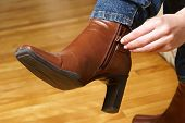 stock photo of ankle shoes  - A woman is zipping her fashionable brown boots - JPG