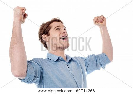 Young Man Celebrating Success With Arms Up