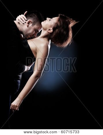 A picture of a young passionate couple dancing over black background