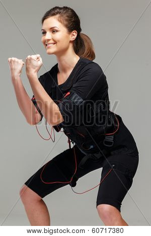 Young woman doing exercise  in Electro Muscular Stimulation EMS training costume
