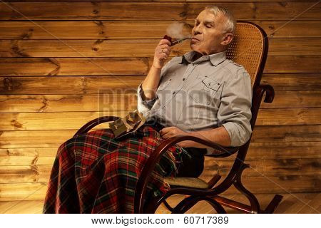 Senior man with smoking pipe sitting on rocking chair in homely wooden interior