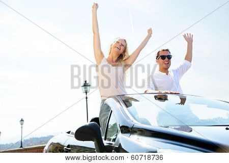 Happy people in car driving on road trip. Young couple having fun dancing and cheering in car driving on travel vacation together. Lifestyle with beautiful cheerful lovers, young woman and man.