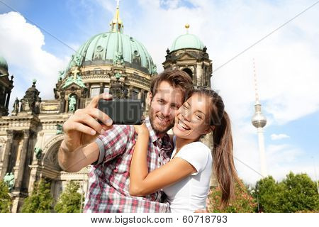 Travel couple selife self portrait, Berlin, Germany. Happy tourists people in front of Berlin Cathedral / Berliner Dom with Fernsehturm / Berlin TV Tower in the background. Asian woman, Caucasian man.