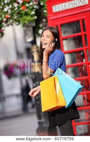 London woman talking happy on smart phone shopping while laughing on mobile phone holding shopping bags by red phone booth. Female shopper smiling in London, England, United Kingdom. Mixed race Asian.