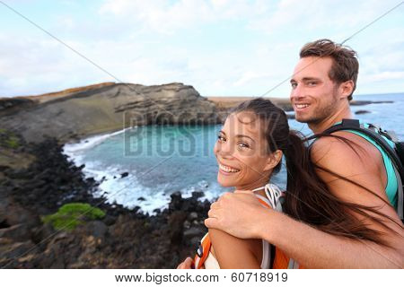 Hiking - travel couple tourist on Hawaii hike. Tourist backpackers walking on Green Sand Beach, Papakolea on Big Island, Hawaii, USA. Interracial young happy couple traveling with backpacks.
