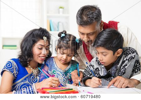 Asian Indian family drawing and painting picture at home. India family lifestyle. Happy parents and children having fun.