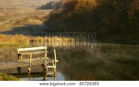 Pontoon on a lake near a forest in autumn