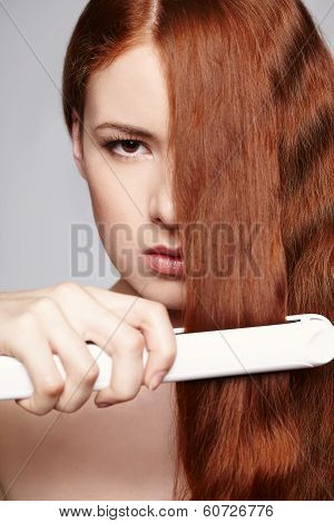 Redheaded woman with hair straightening irons
